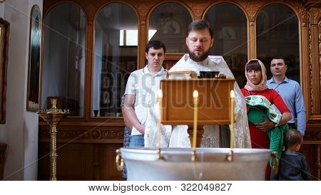 The Sacrament Of Baptism. Orthodoxal Christening The Baby. Children, Mother, Priest And Godfather.