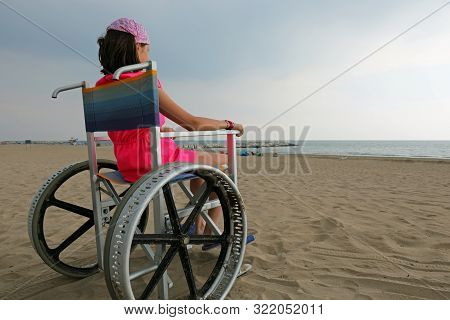 Little Girl On The Wheelchair With Big Wheels To Move On The Sandy Beach In Summer
