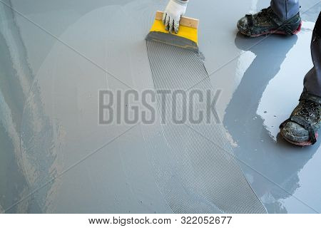 Construction Worker Renovates Balcony Floor And Spreads Watertight Resin And Glue Before Chipping An