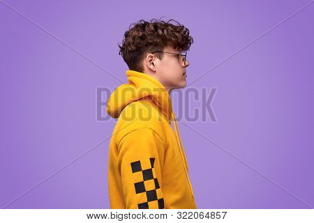 Side View Of Stylish Youngster In Bright Yellow Hoodie And Glasses Standing Against Violet Backgroun