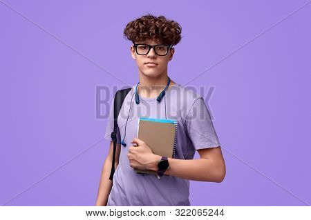 Confident Youngster In Glasses Holding Notepads And Looking At Camera During Studies Against Vibrant