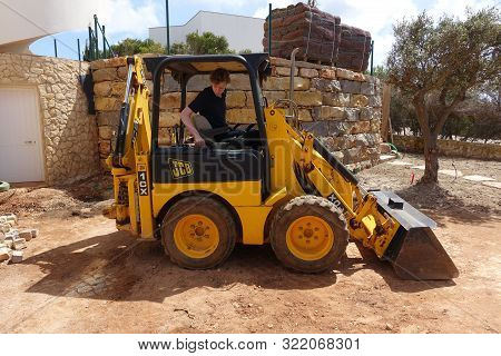 Algarve, Portugal 10 April 2019: A Jcb Mini Digger Being Used To Do Landscaping Work In A Front Gard