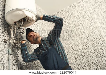 Plumber Installing Electric Heating Boiler. Young Handyman In Uniform Setting Up Electric Heating Bo