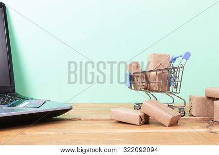 Online Shopping Concept. Shopping Cart, Small Boxes, Laptop And Credit Card On The Desk