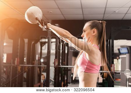 Athletic Woman With A Ponytale Wearing Pink And Black Professional Sportswear Doing Exercises With A