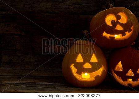 Halloween Pumpkins With Funny Expression. Carved Halloween Pumpkin With Lights Inside On A Black Bac