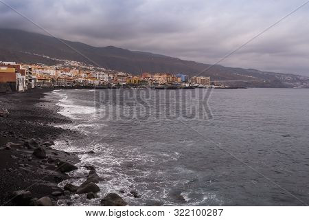 Cloudy Spring Weather. Dark Rocks On The Shore Of Atlantic Ocean. Buildings Of The City In The Backg