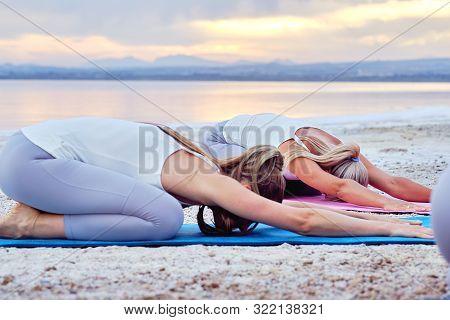 Women Wearing Sportswear Practising Yoga In Nature During Sunset Sunrise On Lake Sea Coast, Yogi Do