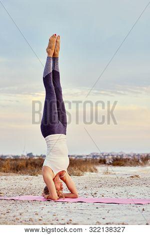Woman Wearing Sportswear Performing Asana On Nature, Yogi Female Doing Hatha Yoga Headstand Or Sirsa