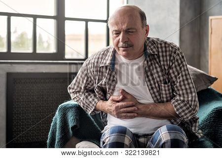 Senior Hispanic Man Is Having Pancreatitis Or Gastritis Or Colitis.