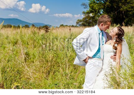 Bride and groom hugging at green field