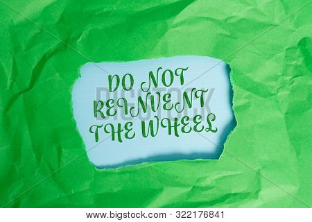Text sign showing Do Not Reinvent The Wheel. Conceptual photo stop duplicating a basic method previously done Green crumpled ripped colored paper sheet centre torn colorful background. poster