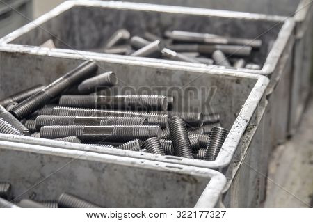 Large Number Of Metal Studs With Thread Randomly Lie In A Plastic Box, Close-up