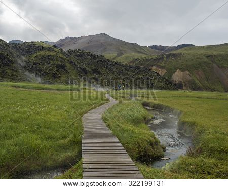 Wooden path to natural hot spring with group of tourist people relaxing in a thermal baths in Landmannalaugar camp site, Iceland. Grass meadow, lava fields and mountains in background poster