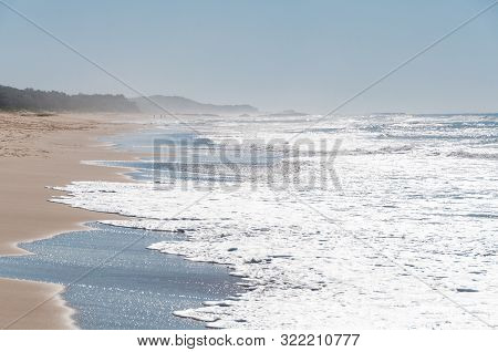 Epic Seascape View With Long Beach With Sand Shore And Mild Glistening Waves. Summer Beach Vacation