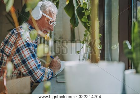 Smiling Man Listening To Music And Making Notes Stock Photo