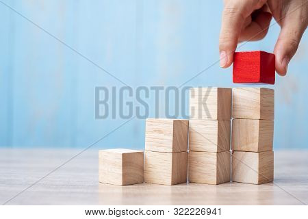 Businessman Hand Placing Or Pulling Red Wooden Block On The Building. Business Planning, Risk Manage
