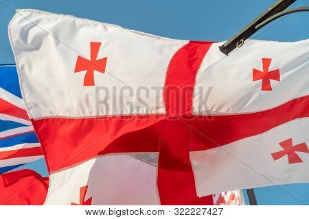 Flag Of Georgia And The United Kingdom Flying In The Wind Against A Blue Sky. The Concept Of Diploma