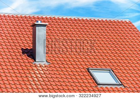 Chimney And Window On Clean Roof Of Residential House. Steel Home Chimney Close-up In Summer. Modern