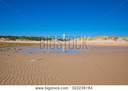 Lighthouse Of Trafalgar Cape Reflected In Water On Sand Beach