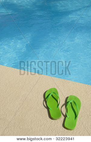 Pair of bright green flip flops at the pools edge