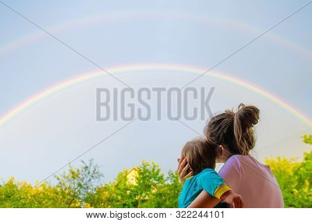 Mom With A Child Looks At The Rainbow. Mom And Son On The Background Of Motherhood. Look At The Rain