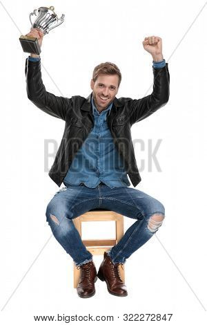 attractive casual man with black leather jacket is sitting on a wooden chair holding his hands up in the air with his cup thrilled on white studio background