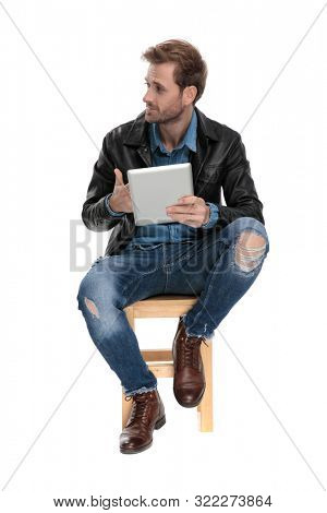 sexy casual man with black leather jacket is sitting on a wooden chair holding a tablet in his hand and looking to a side cocky on white studio background