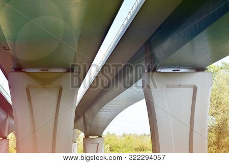 Bottom View Of A Huge Flyover Motorway, Blue Sky, Large Pillars With Sunlight.