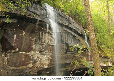 Waterfall Across The Rocks Of North Carolina Forest Along The Blue Ridge Parkway In A Heavily Wooded