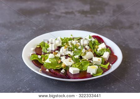 Dietary Salad Of Beetroot, Arugula, Feta Cheese, Pumpkin Seeds With Olive Oil On A Dark Background C