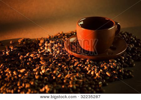 Brown coffee cup on coffee beans with brown background