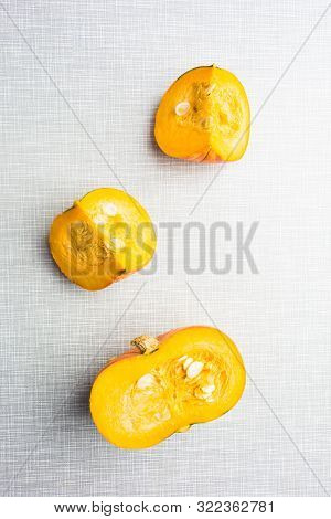 Natural Sweet Autumn Orange Vegetable. Cut Pieces Of Pumpkin Over Textured Background. Copy Space. F