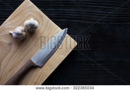 Knife Garlic Board On  Black Wooden Background