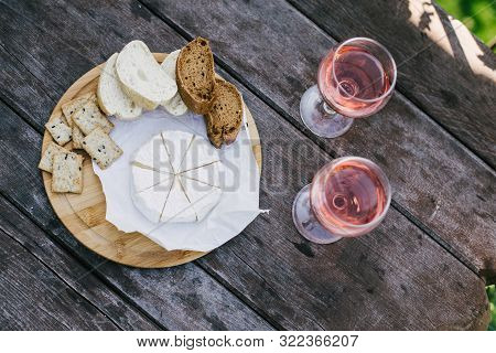 Still Life With Camembert Cheese, Fresh Bread And Crackers On Wooden Tray And Two Glasses Of Rose Wi