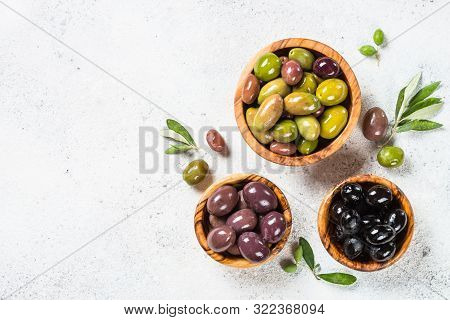 Natural Greek Olives In Wooden Bowl On White Stone Background. Top View With Copy Space.