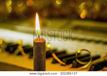 Candle Near The Piano, Which Is Decorated With Christmas Shiny Garlands