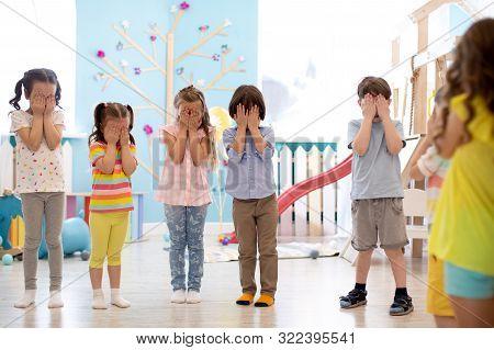 Kindergarten Pupils Kids Cover Their Eyes At The Instruction Of Their Teacher During A Class Activit