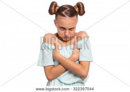 Emotional portrait of offended teen girl with crossed arms. Unhappy sad child, isolated on white background. Cute caucasian young teenager folded hands in bad mood.