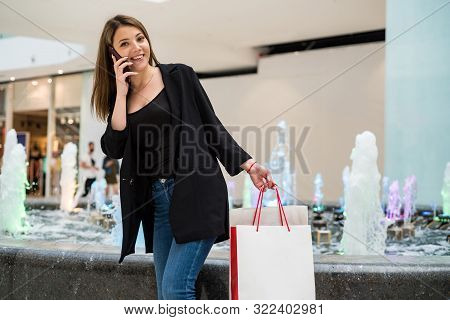 Beautiful Brown-haired Girl With Shopping Bags Uses Phone In Mall