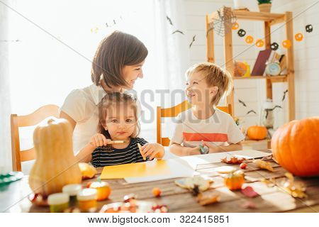 Family Mother And Child Daughter In Hat Witch Are Preparing For Halloween Carve A Pumpkin And Decora
