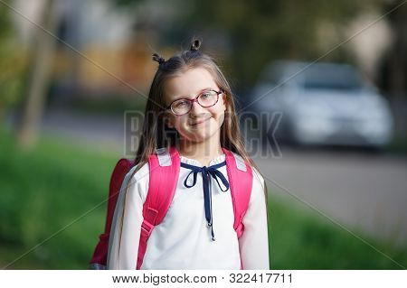 Portrait Of Smiling Schoolgirl With Backpack Outdoors. Child Girl Looking At Camera. Selective Focus