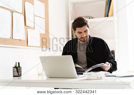 Image of a concentrated professional man architect in office reading book work with paper using laptop computer.