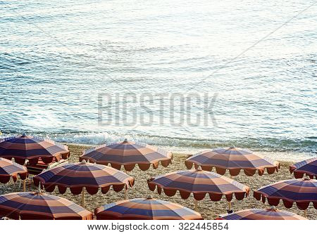 Sun Umbrellas Open Early In The Morning On A Beach By The Sea. Beach Holidays During The Summer Seas