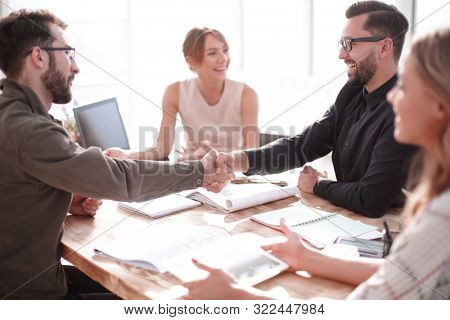 smiling business partners shaking hands at a business meeting.
