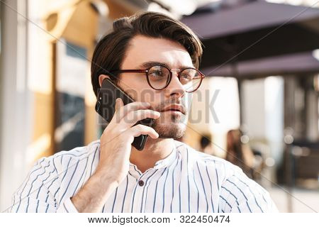 Photo of perplexed caucasian man wearing eyeglasses talking on cellphone while working in cafe outdoors poster