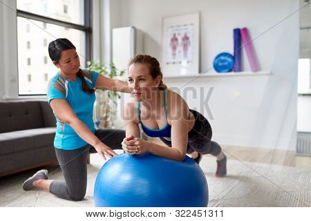 Chinese Woman Personal Trainer During A Workout Session With An Attractive Blond Client In A Bright