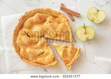 Apple Pie On The Parchment With Fresh Apples And Cinnamon Sticks
