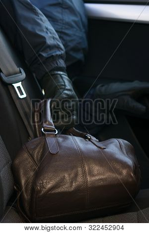 Thief's Hand Steals Brown Leather Bag From Car Backseat