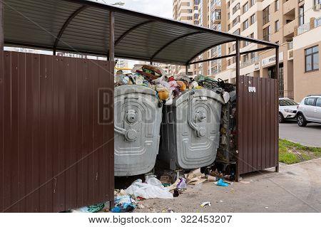Minsk, Belarus - July 20, 2019: Orderly Bin With Trash In It, Trash On Ground In The Courtyard Of An